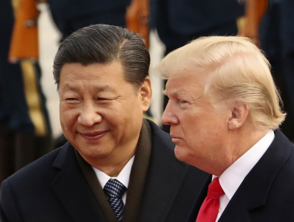 FILE - In this Nov. 9, 2017, file photo, U.S. President Donald Trump and Chinese President Xi Jinping participate in a welcome ceremony at the Great H...
