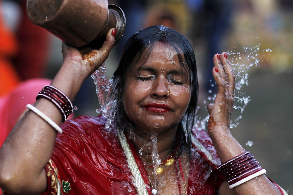 In this Nov. 13, 2018, file photo, a Nepalese woman takes a holy bath on the banks of the Bagmati River during Chhath Puja festival in Kathmandu, Nepa...