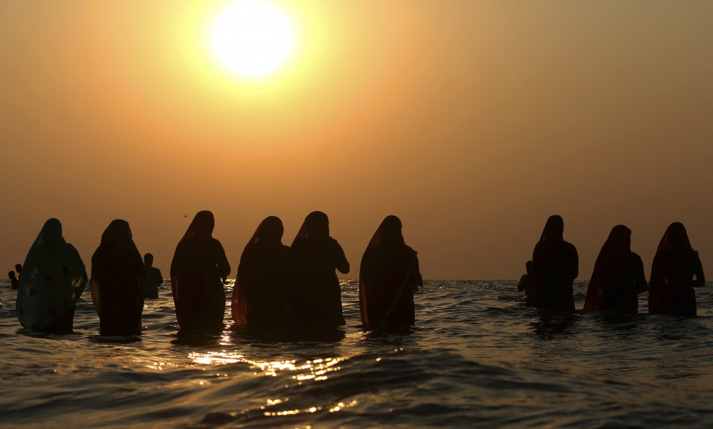 In this Nov. 13, 2018, file photo, Hindu devotees offer prayers standing in the waters of the Arabian Sea at sunset during Chhath Puja festival in Mum...