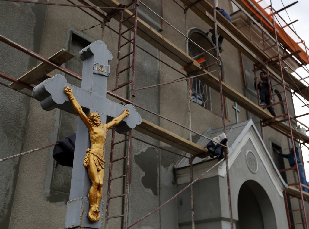 In this Thursday, Oct. 18, 2018 photograph, a man works on scaffolding outside a Catholic Church in Chop, Ukraine. A new education law that could prac