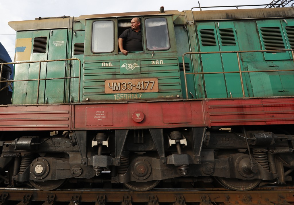 In this Thursday, Oct. 18, 2018 photograph, a railroad engineer looks out of a locomotive at a railroad track gauge changer in Chop, Ukraine. A new ed...