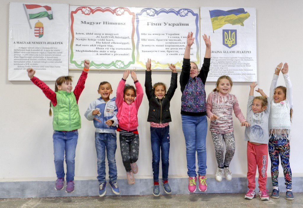 In this Friday, Oct. 19, 2018 photograph, children jump in front of posters with the Hungarian and Ukrainian anthems and national symbols at the Velyk...