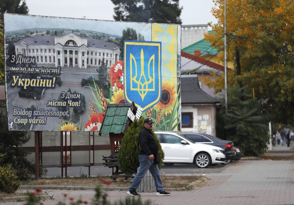 """In this Thursday, Oct. 18, 2018 photograph, a man passes by a poster saying """"Happy birthday, Chop city!"""" in Ukrainian, Russian and Hungarian, in Chop,"""