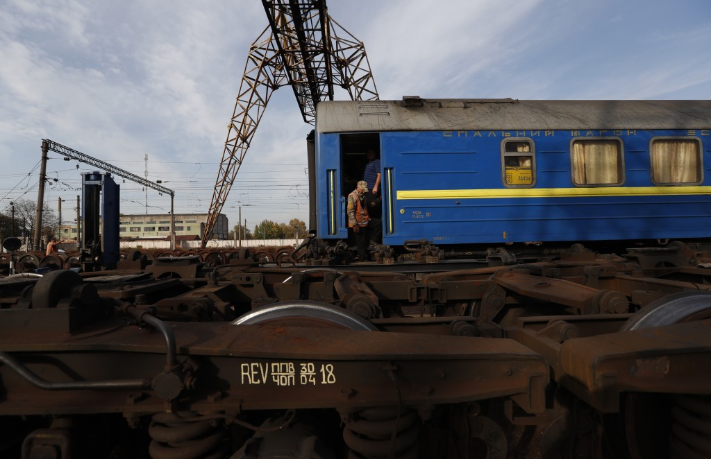 In this Thursday, Oct. 18, 2018 photograph, a worker descends from a carriage at a railroad track gauge changer in Chop, Ukraine. A new education law ...