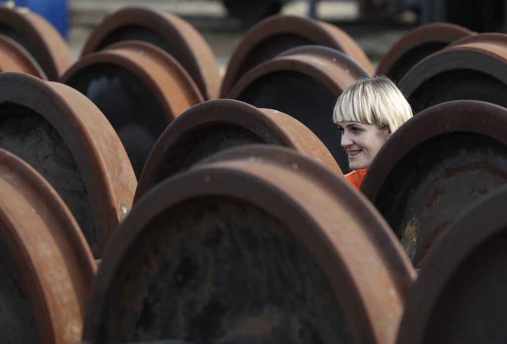 In this Thursday, Oct. 18, 2018 photograph a female worker smiles at a railroad track gauge changer in Chop, Ukraine. A new education law that could p...