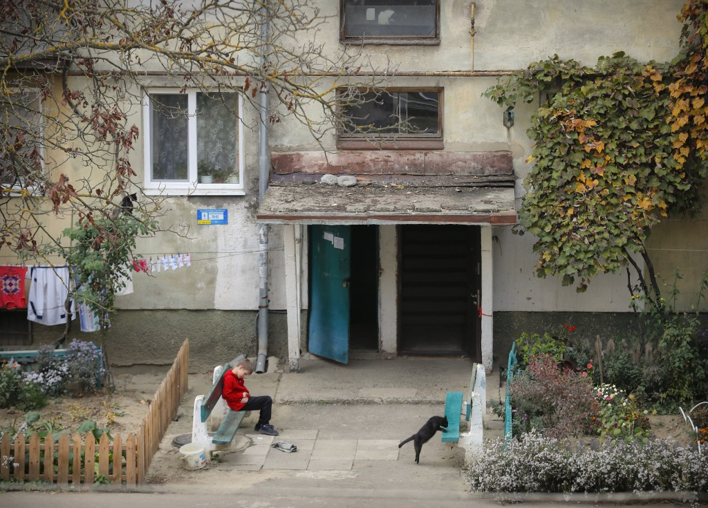 In this Thursday, Oct. 18, 2018 photograph, a boy sits outside an apartment building in Chop, Ukraine. A new education law that could practically elim