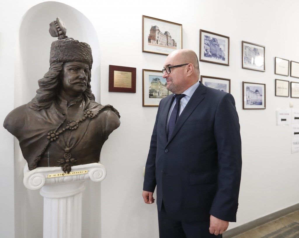 In this Friday, Oct. 19, 2018 photograph Laszlo Brenzovics, president of the Transcarpathian Hungarian Cultural Association stands next to a bust of H...