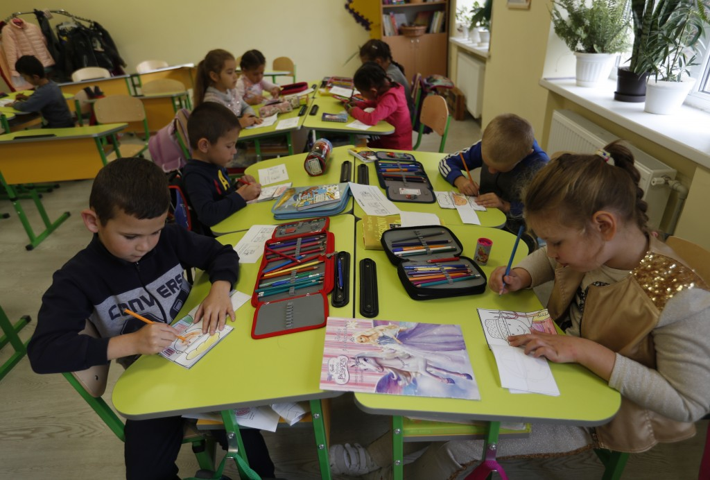 In this Friday, Oct. 19, 2018 photograph, children attend class at the Velyka Dobron High School in Velyka Dobron, Ukraine. A new education law that c