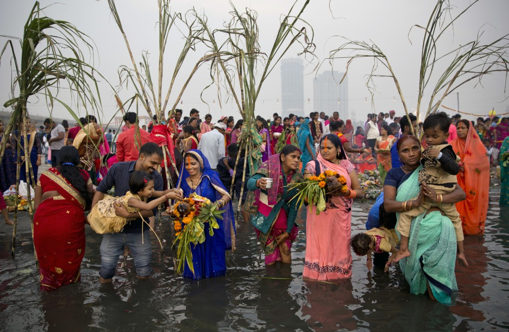 In this Tuesday, Nov. 13, 2018, file photo, Hindu devotees pray to the Sun god as they stand in knee-deep waters in River Yamuna, during the Chhath fe