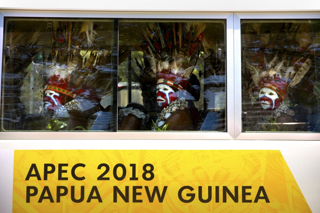In this Nov. 14, 2018, file photo, men in traditional dress ride a shuttle bus ahead of the APEC Economic Leaders' Week Summit in Port Moresby, Papua ...