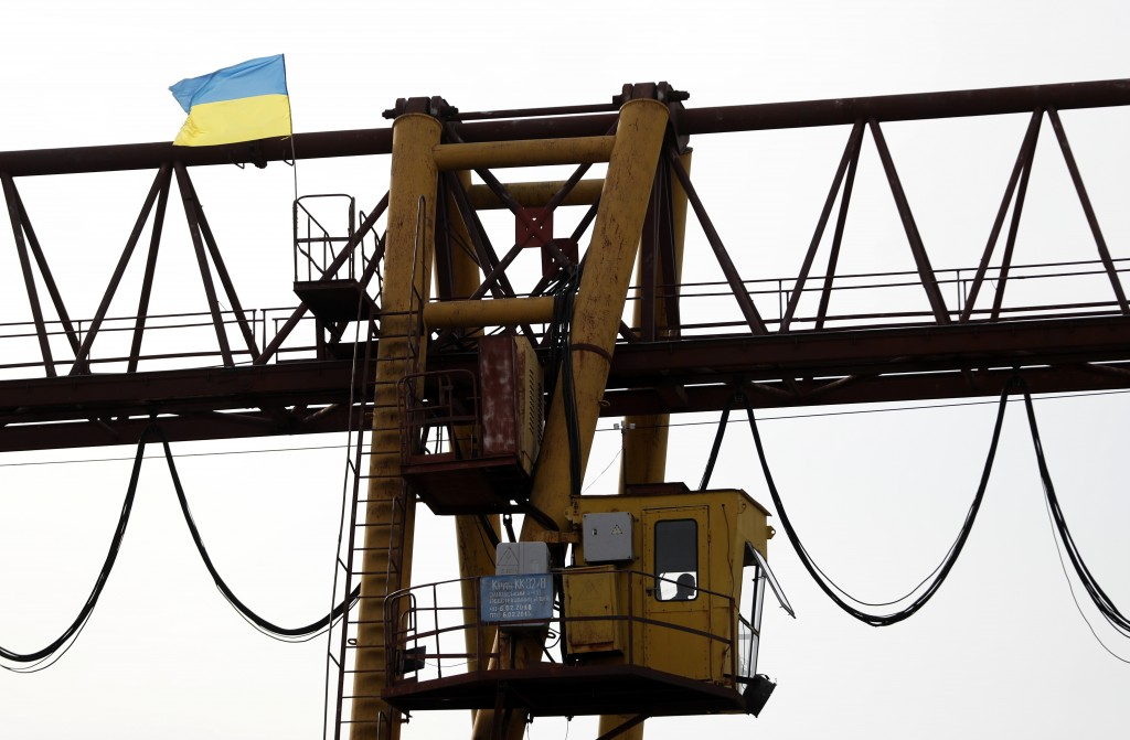 In this Friday, Oct. 19, 2018 photograph, a man operates a loading crane at a logistics center in Chop, Ukraine. A new education law that could practi