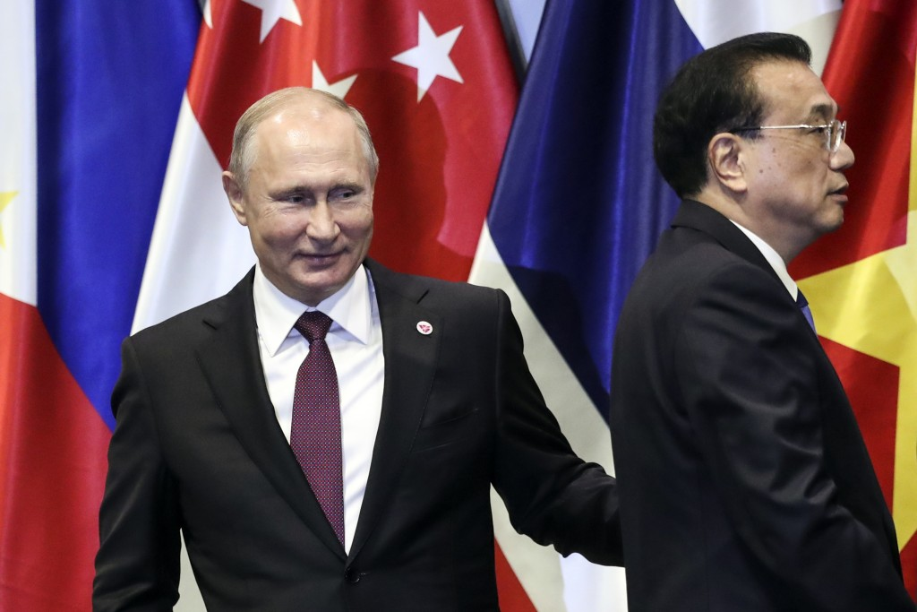 In this Thursday, Nov. 15, 2018, file photo, Russian President Vladimir Putin, left, and Chinese Premier Li Keqiang interacts on stage after a group p...