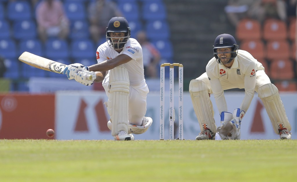 Sri Lankan Dhananjaya de Silva plays a shot as England's wicketkeeper Ben Foakes watches during the second day of the second test cricket match betwee...