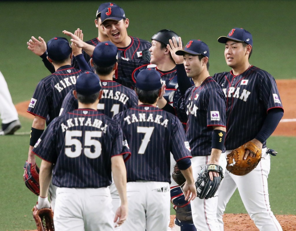 All Japan closer Yasuaki Yamasaki, back facing camera, celebrates with teammates on the mound after beating MLB All-Stars 4-1 in Game 6 at their All-S...
