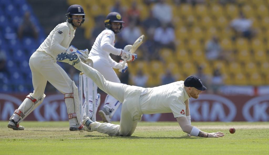 England's Ben Stokes, bottom, dives to stop a ball as wicketkeeper Ben Foakes and Sri Lankan batsman Dhananjaya de Silva watch the ball as they filed