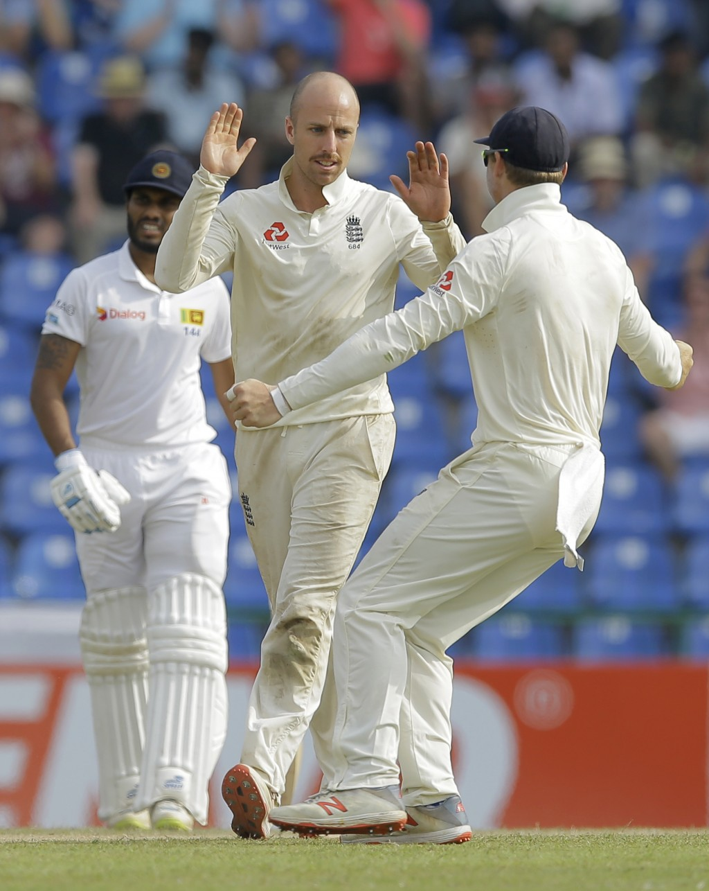 England's Jack Leach, center, celebrates the wicket of Sri Lanka's Dilruwan Perera with teammates during the second day of the second test cricket mat