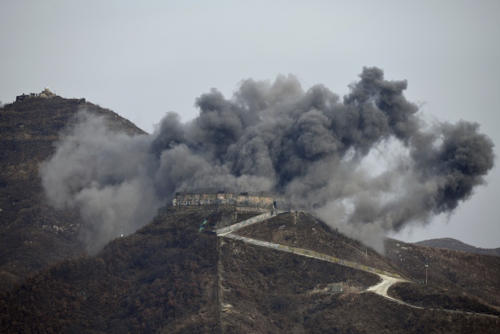 In this Thursday, Nov. 125, 2018, file photo, smoke from an explosion rises as part of the dismantling of a South Korean guard post in the Demilitariz...