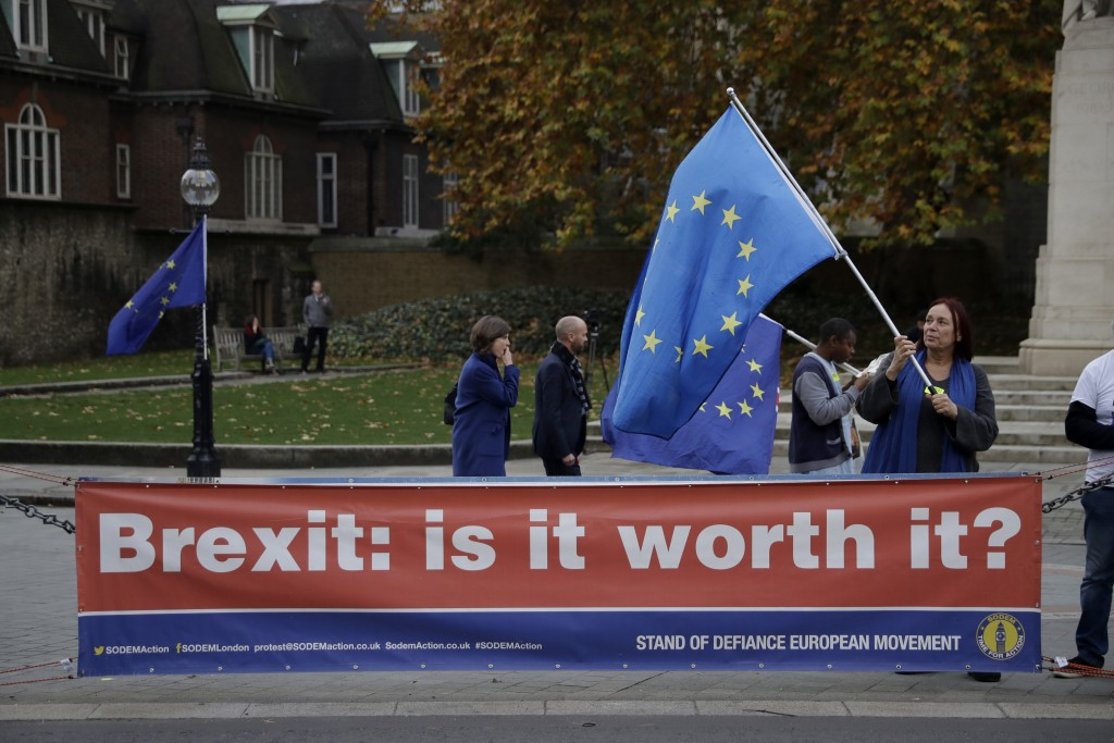 An anti-Brexit supporter holds a European flag by a banner across the street from the Houses of Parliament in London, Thursday Nov. 15, 2018. Leading ...