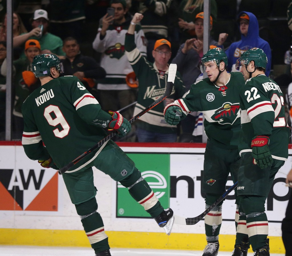 Minnesota Wild center Charlie Coyle (3) celebrates his goal with Mikko Koivu (9) and Nino Niederreiter (22) during the first period of an NHL hockey g...