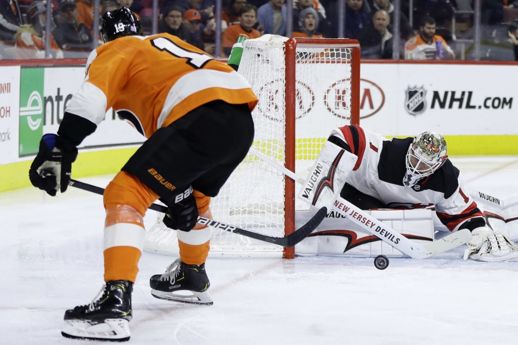 Philadelphia Flyers' Nolan Patrick, left, takes a shot against New Jersey Devils' Keith Kinkaid during the second period of an NHL hockey game, Thursd...