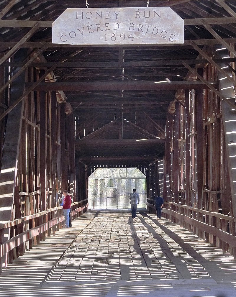 This undated photo provided by Glenn Harrington shows people walking along the Honey Run Covered Bridge in Butte Creek Canyon in Paradise, Calif. The