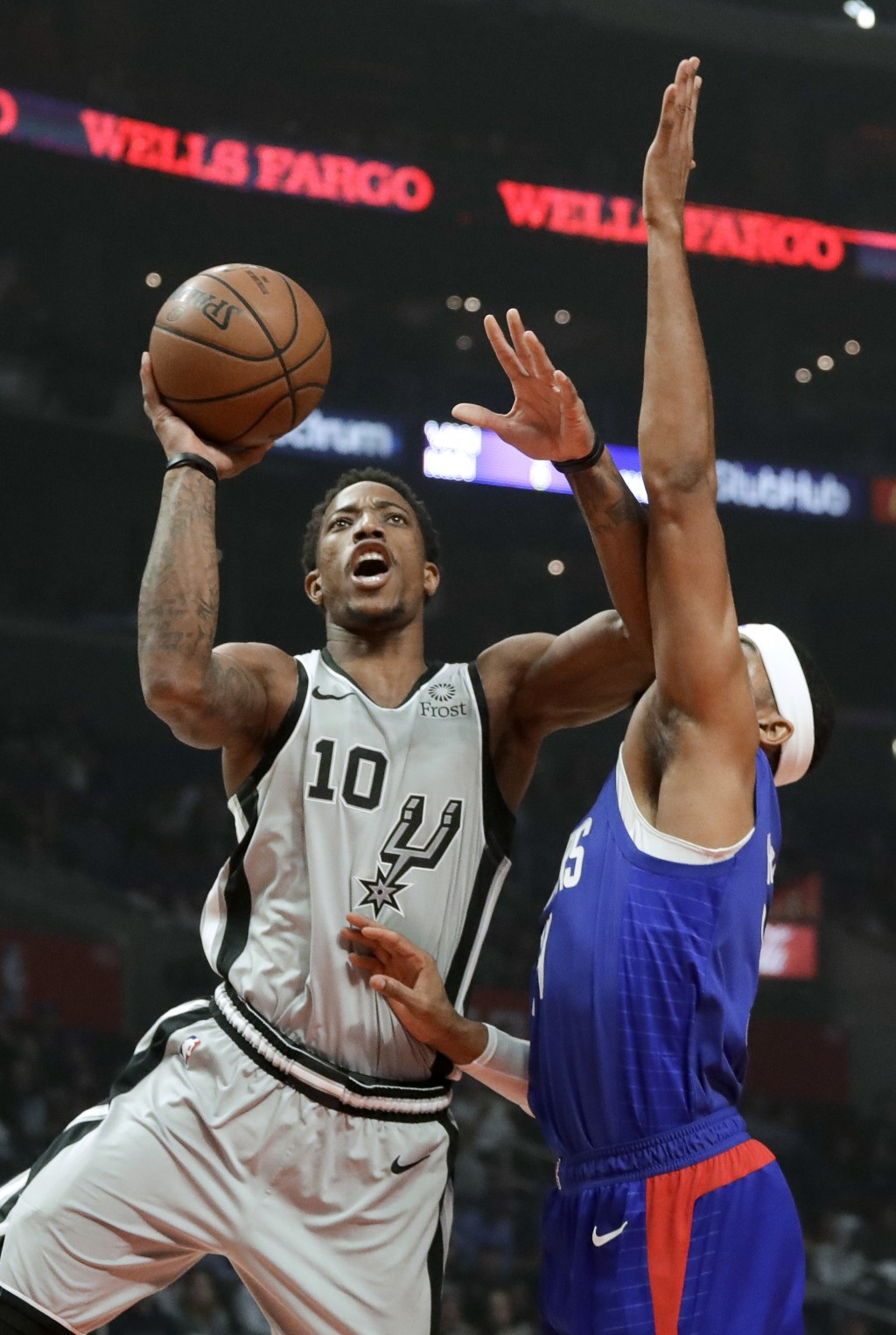 San Antonio Spurs guard DeMar DeRozan, left, drives to the basket past Los Angeles Clippers forward Tobias Harris during the first half of an NBA bask...