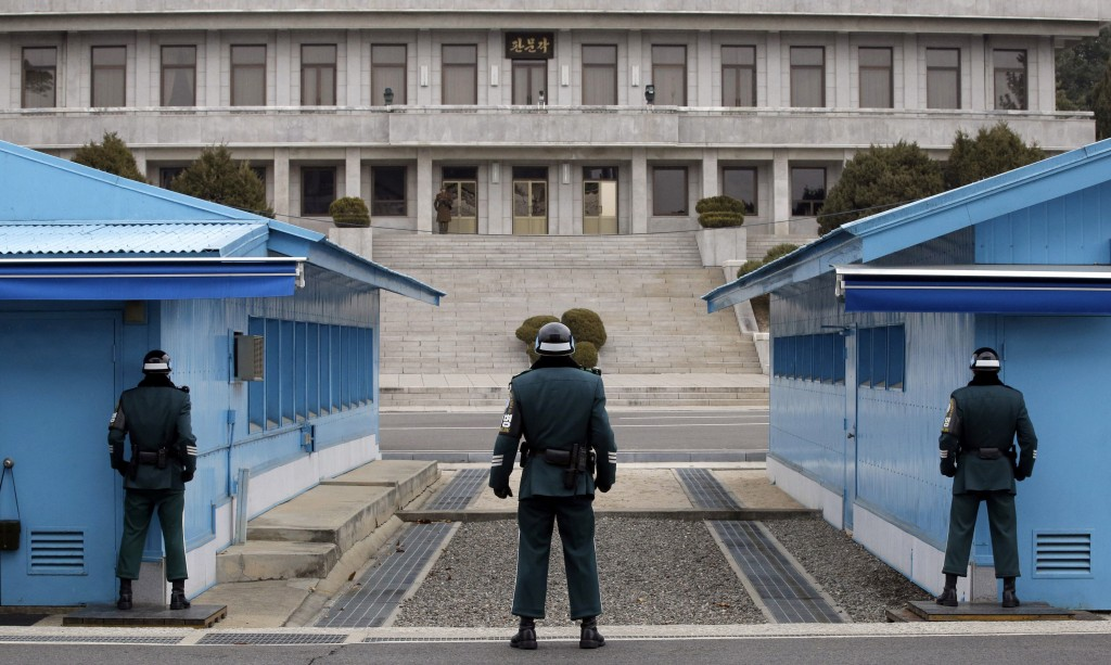 FILE - In this March 12, 2014, file photo, a North Korean soldier, center top, looks at the southern side as three South Korean soldiers guard at the