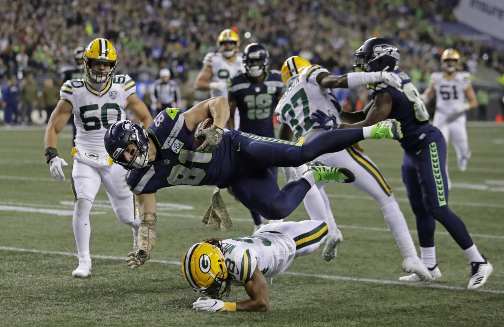 Seattle Seahawks tight end Nick Vannett (81) gets horizontal above Green Bay Packers cornerback Tramon Williams, lower-center, as Vannett carries the ...