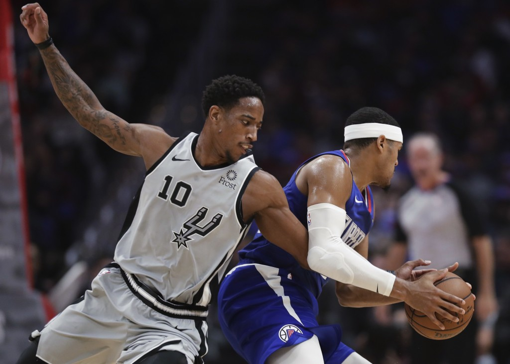 San Antonio Spurs guard DeMar DeRozan tries to steal the ball from Los Angeles Clippers forward Tobias Harris during the first half of an NBA basketba