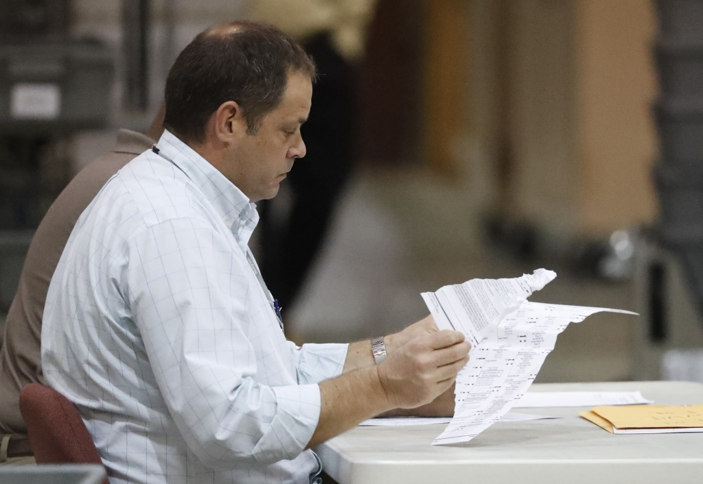 Employees look through damaged ballots at the Supe...