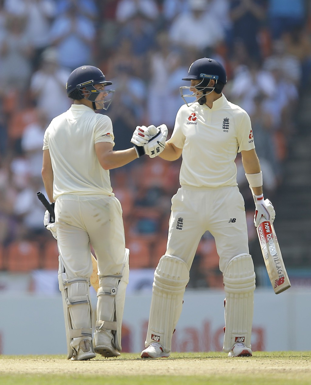 England's captain Joe Root, right, congratulates Rory Burns for scoring a half century during the third day's play of the second test cricket match be...