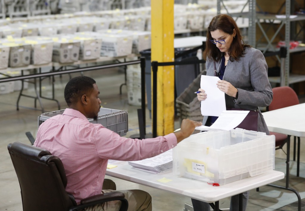 A Republican party observer, right, watches as an employee at the Palm Beach County Supervisor Of Elections office goes through a stack of damaged bal...