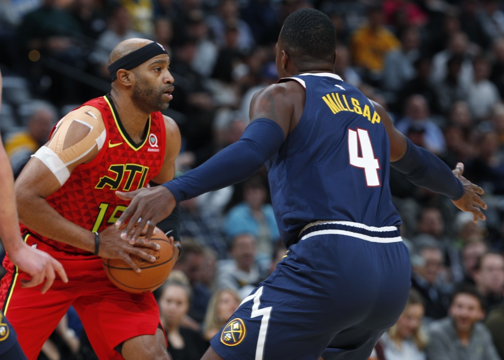 Atlanta Hawks forward Vince Carter, left, looks to pass the ball past Denver Nuggets forward Paul Millsap in the first half of an NBA basketball game