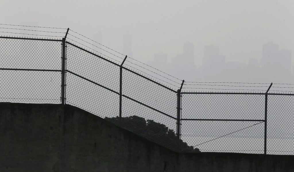 The skyline is obscured by smoke and haze from wildfires and is barely visible behind the prison exercise yard fence on Alcatraz Island Thursday, Nov....