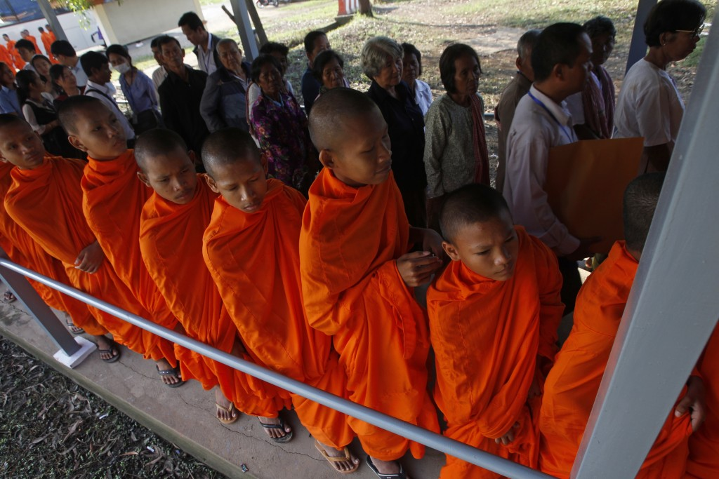 Cambodian Buddhist monks wait in queue to enter into the courtroom before the hearings against two former Khmer Rouge senior leaders, at the U.N.-back...
