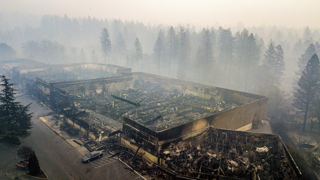 FILE - In this Thursday, Nov. 15, 2018 file photo smoke hangs over the scorched remains of Old Town Plaza following the wildfire in Paradise, Calif. M