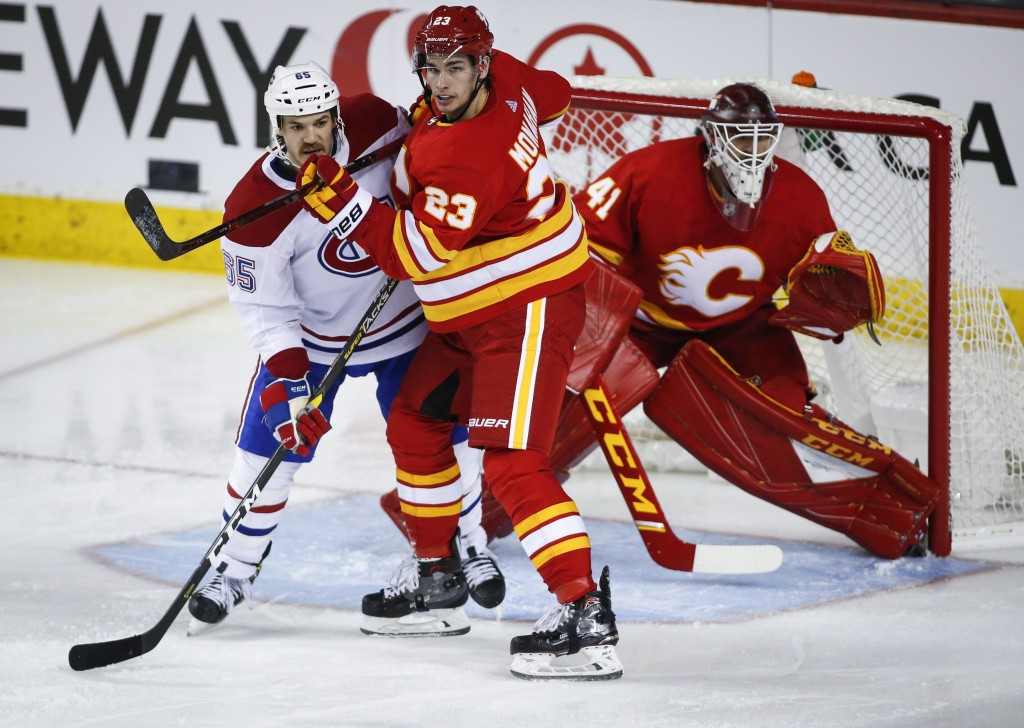 Montreal Canadiens' Andrew Shaw, left, tangles with Calgary Flames' Sean Monahan, center, as goalie Mike Smith looks past them during the third period