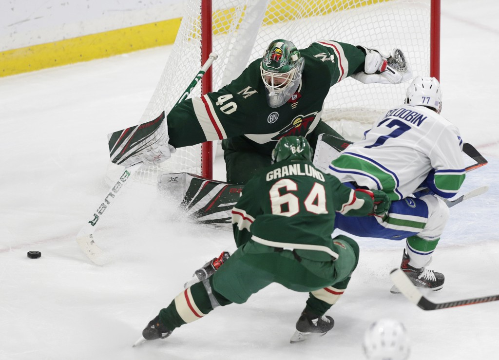 Minnesota Wild goalie Devan Dubnyk (40) makes a save on a shot by Vancouver Canucks right wing Nikolay Goldobin (77) with Wild right wing Mikael Granl
