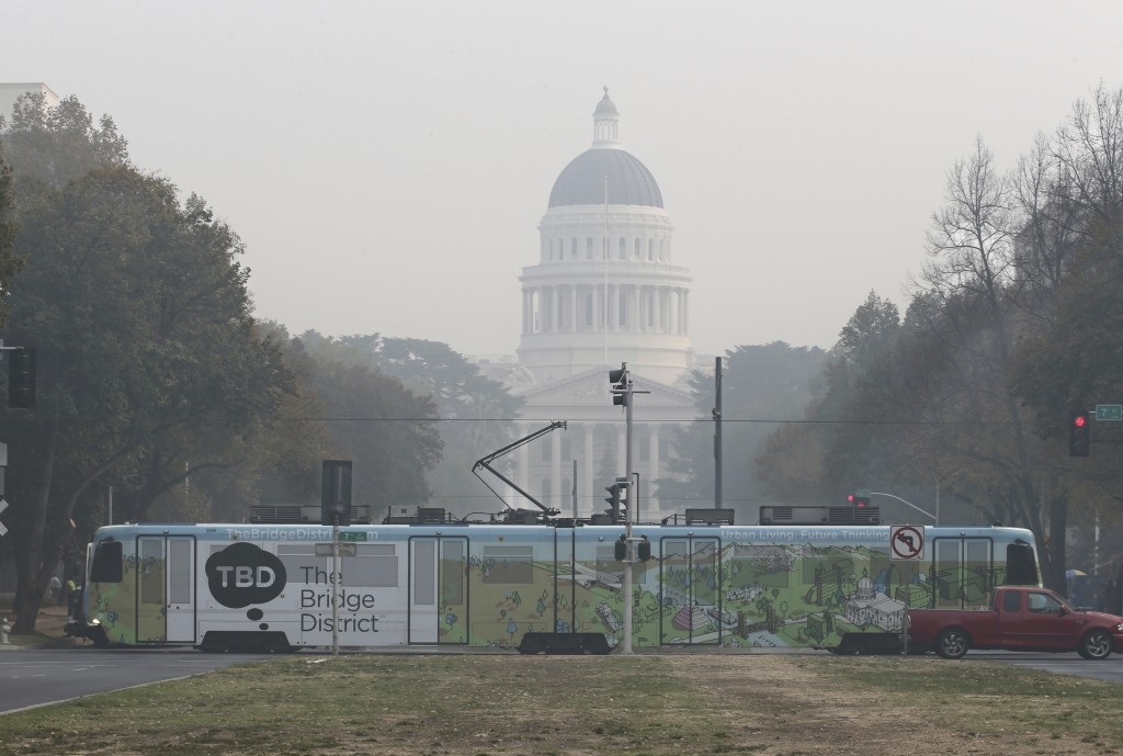 A light-rail train passes in front of the smoke shrouded state CapitolThursday, Nov. 15, 2018, in Sacramento, Calif. Smoke from the Camp Fire that bur