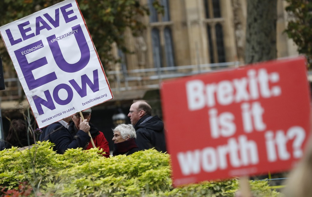Pro and anti Brexit protesters hold placards as they vie for media attention near Parliament in London, Friday, Nov. 16, 2018.  Britain's Prime Minist...