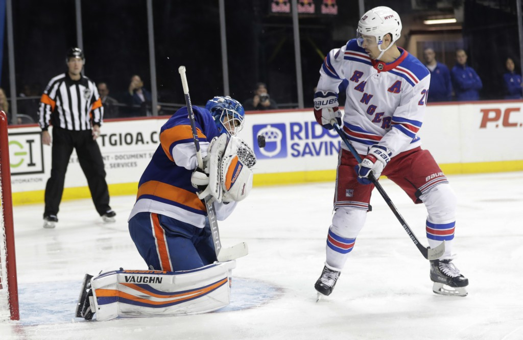 New York Rangers' Chris Kreider (20) watches as New York Islanders goaltender Thomas Greiss (1) stops a shot during the first period of an NHL hockey