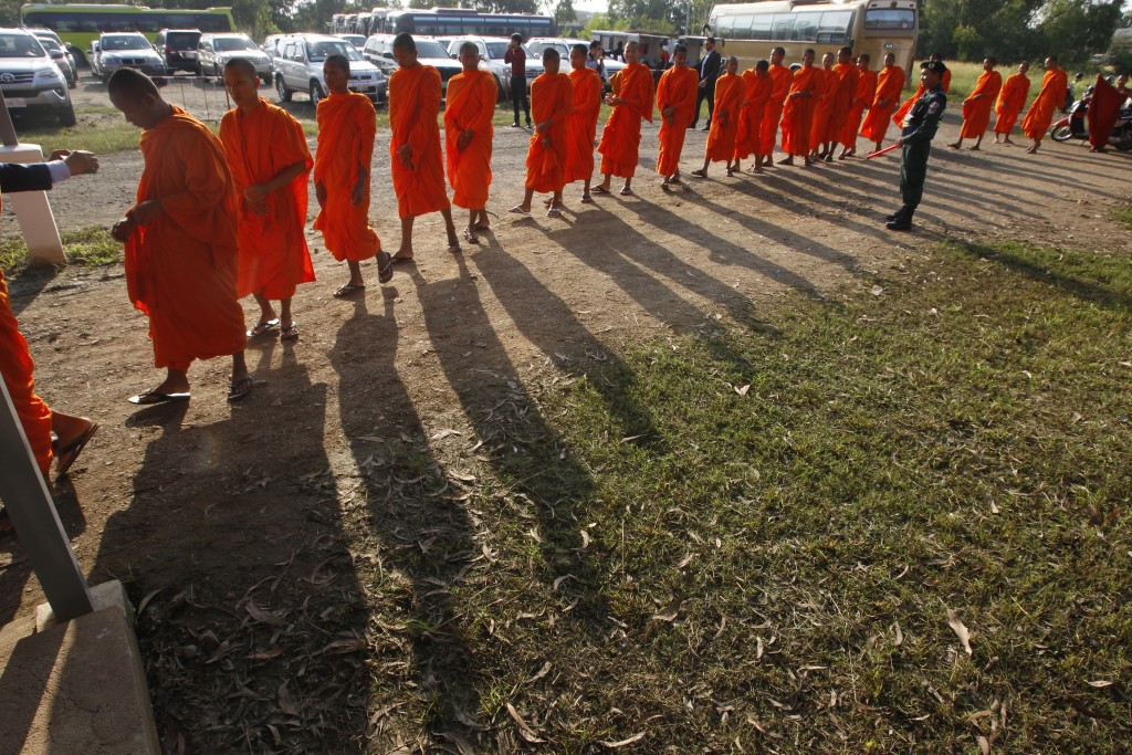 Cambodian Buddhist monks wait in queue for entering into the courtroom before the hearings against two former Khmer Rouge senior leaders, at the U.N.-...