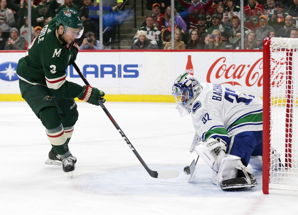 Minnesota Wild center Charlie Coyle (3) is stopped by Vancouver Canucks goalie Richard Bachman (25) during the first period of an NHL hockey game Thur...