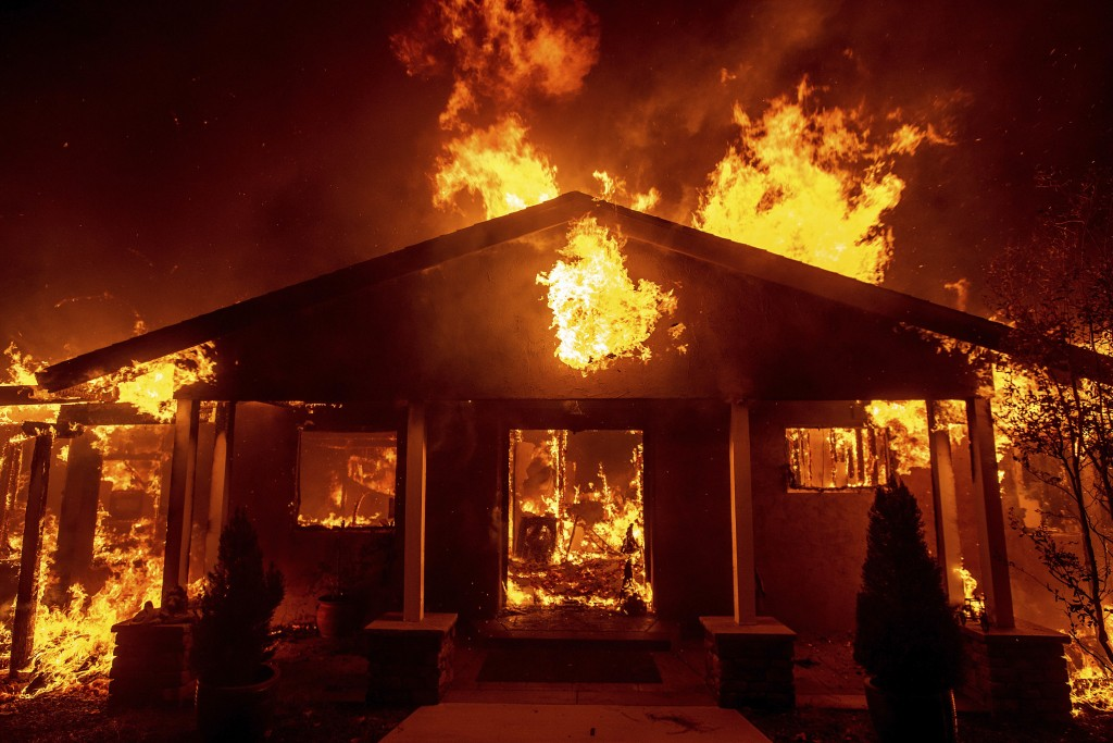FILE - In this Thursday, Nov. 8, 2018 file photo, a home burns as the Camp Fire rages through Paradise, Calif. This town of 27,000 was destroyed in th