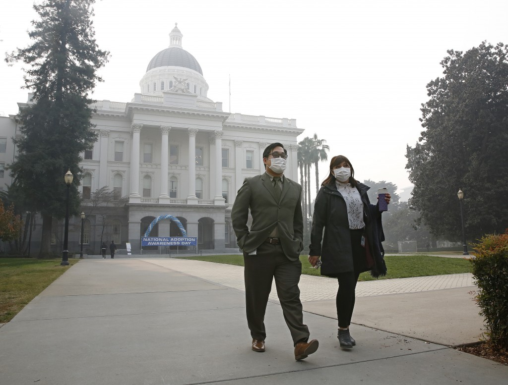 Tashi Nacario and Samantha Salas don masks to deal with the smoke from the Camp Fire that shrouds the state Capitol Thursday, Nov. 15, 2018, in Sacram...