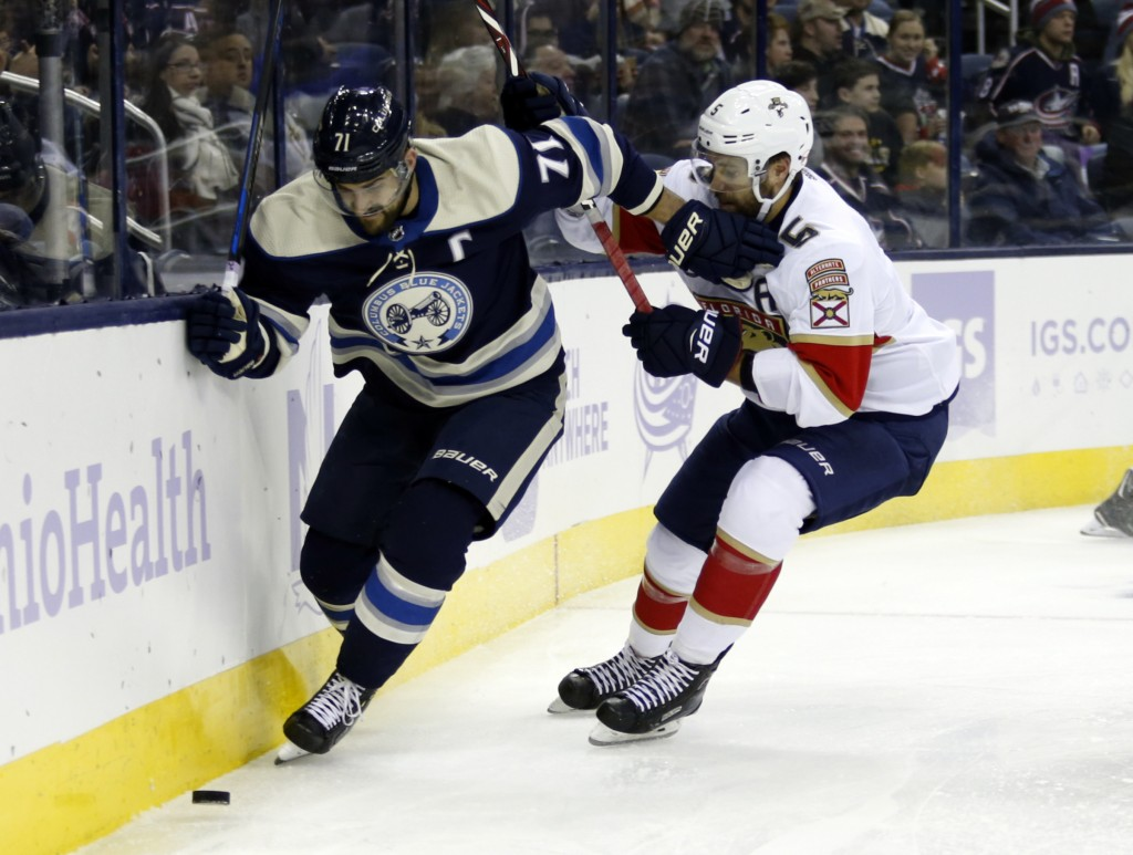 Columbus Blue Jackets forward Nick Foligno, left, works against Florida Panthers defenseman Aaron Ekblad during the second period of an NHL hockey gam...