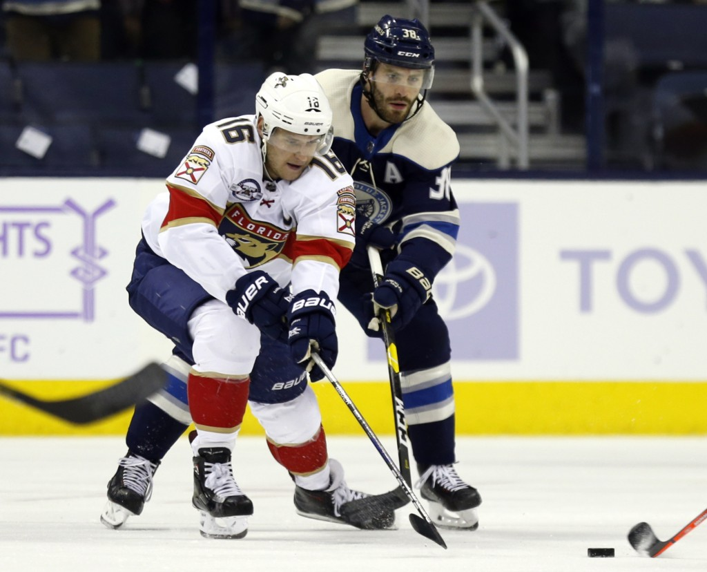 Florida Panthers forward Aleksander Barkov, left, of Finland, works against Columbus Blue Jackets forward Boone Jenner during the first period of an N