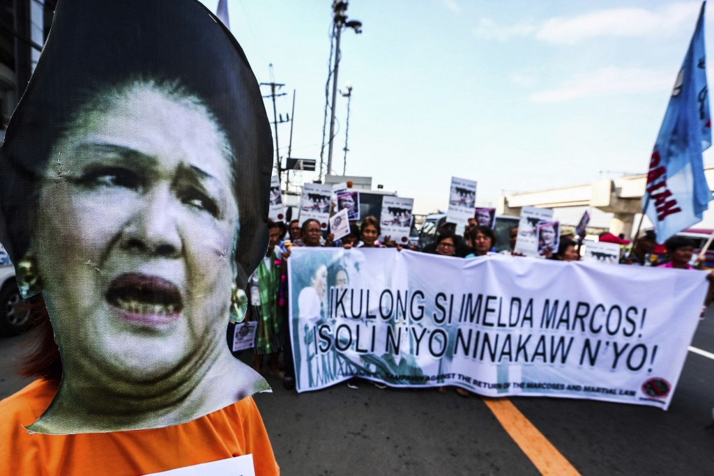 CORRECTS DATE - Protesters display a banner as they picket the anti-graft court Sandiganbayan as former Philippine First Lady Imelda Marcos was ordere