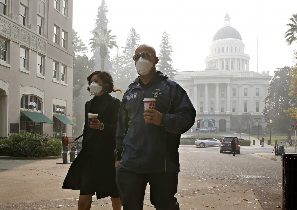 Mattelin Bautista and Stephen Penner don masks to deal with the smoke from the Camp Fire that shrouds the state Capitol Thursday, Nov. 15, 2018, in Sa