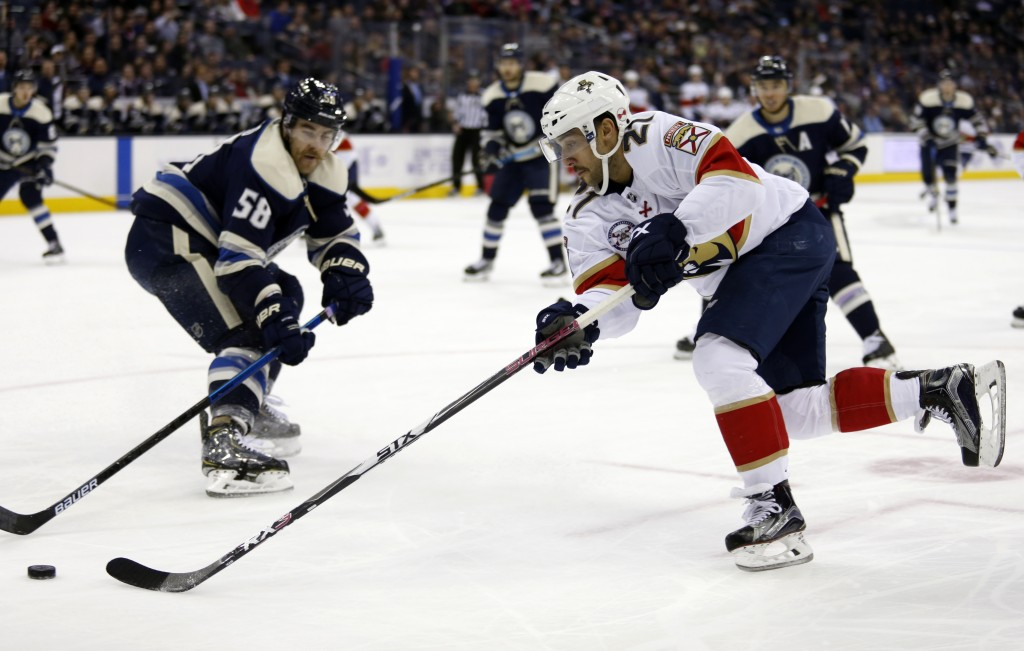 Florida Panthers forward Vincent Trocheck, right, chases the puck against Columbus Blue Jackets defenseman David Savard during the first period of an